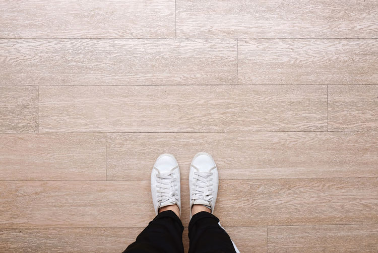 Low section of man standing on hardwood floor