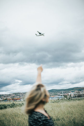 Rear view of airplane flying over cityscape against sky