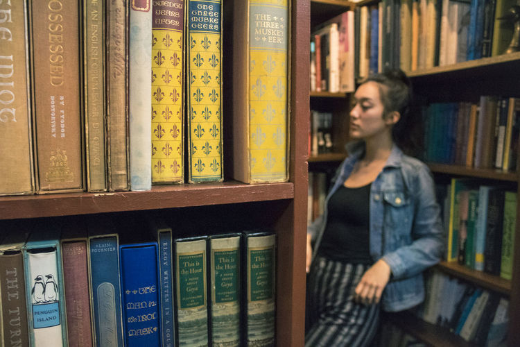 Young woman reading book in shelf