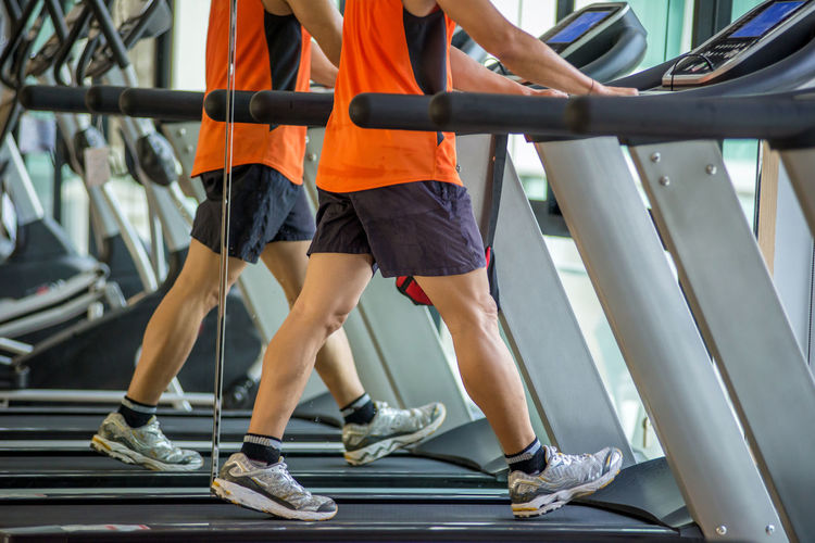 Low section of men walking on treadmills in gym