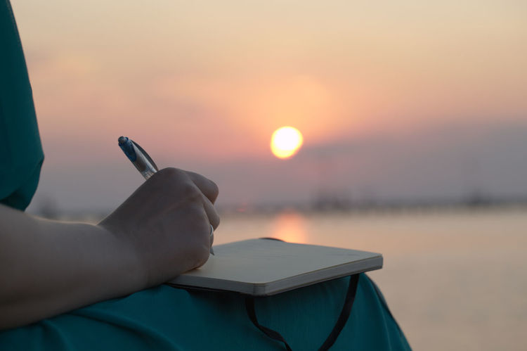 Alone Beach Caucasian Close Up Detail Diary Handwritten Holding Notes Outdoors Paper Pen Sea Serenity Sun Sunlight Sunset Water Woman Write Writing