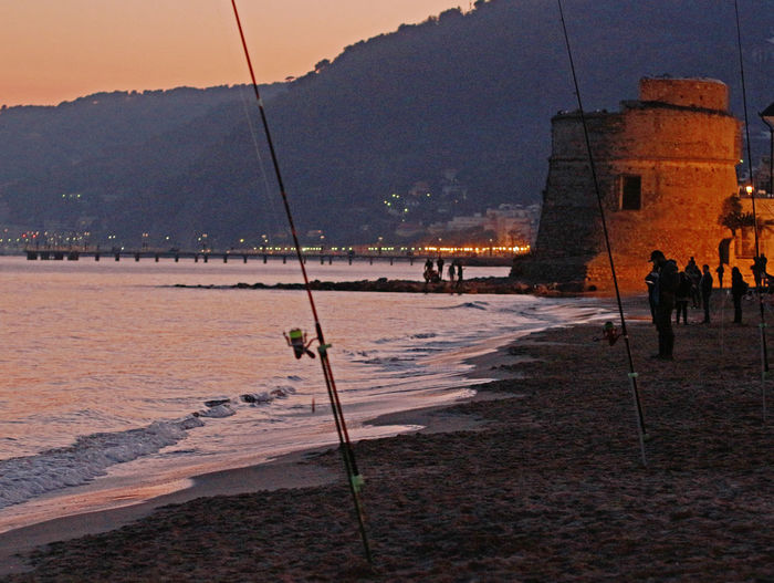 Alassio Alassiobay Alassiobeach Architecture Beach Building Exterior Built Structure Day Evening Evening Sky Fishers Fishing Fishing Contest Fishing Pole Fishing Poles Fishing Time Nature No People Outdoors Sand Sea Sky Sunset Torrione