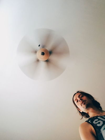 Low angle view of man against spinning ceiling fan at home