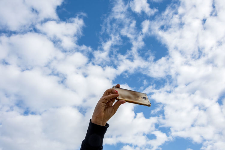 Blue Cellphone Cloud - Sky Clouds Clouds And Sky Daydreaming Hand Holding Human Body Part Leisure Activity Low Angle View Mobile Love Motion Selfie Sky Human Hand EyeEm EyeEm Gallery EyeEm Team Adults Only Uniqueness Mobile Conversations