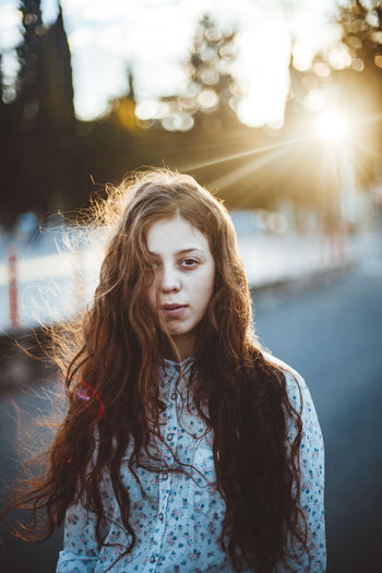 Beautiful Woman Brown Hair Contemplation Focus On Foreground Front View Hair Hairstyle Leisure Activity Lens Flare Lifestyles Long Hair Looking At Camera One Person Outdoors Portrait Real People Standing Sunlight Teenager Waist Up Warm Clothing Women Young Adult Young Women Summer Road Tripping The Portraitist - 2018 EyeEm Awards A New Beginning
