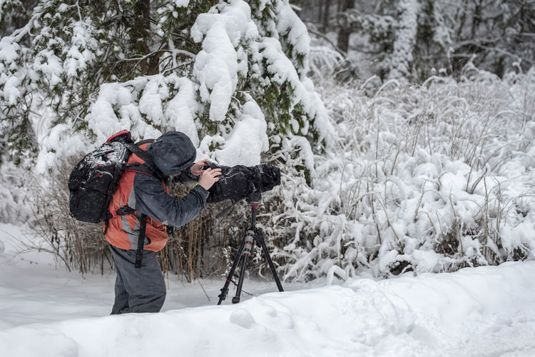 Behind the scene. Cameraman with video camera on tripod, shooting the film scene at outdoor location, on nature, forest, on a cold winter snowy day Snow Winter Cold Temperature Tree One Person Leisure Activity Nature Day White Color Lifestyles Outdoors Snowing Behind Behind The Scenes CameraMan Video Video Camera Tripod Film Winter Cinema MOVIE Shooting Nature Camera