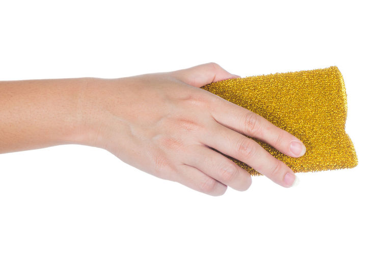 Cropped Hand Holding Cleaning Sponge Against White Background