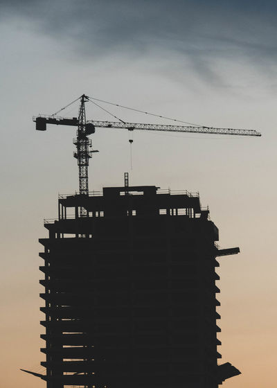 Low angle view of silhouette crane by building against sky