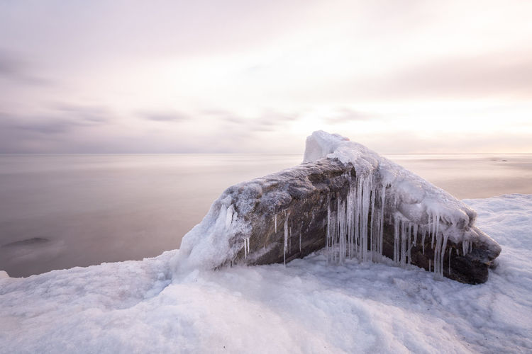 Dilapidated structure covered in ice on the lakeshore