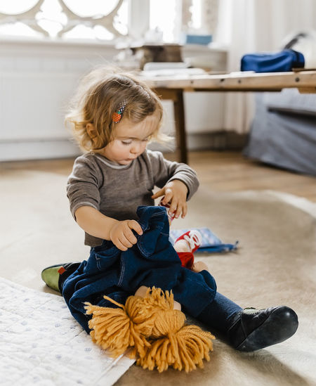 Cute Girl Playing With Toys On Floor At Home