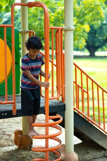 Full length of girl standing on slide at playground