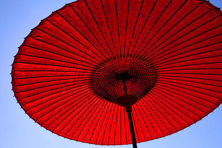 Low angle view of red paper umbrella against sky