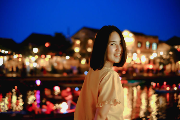 Portrait of smiling woman standing by river in illuminated city at night