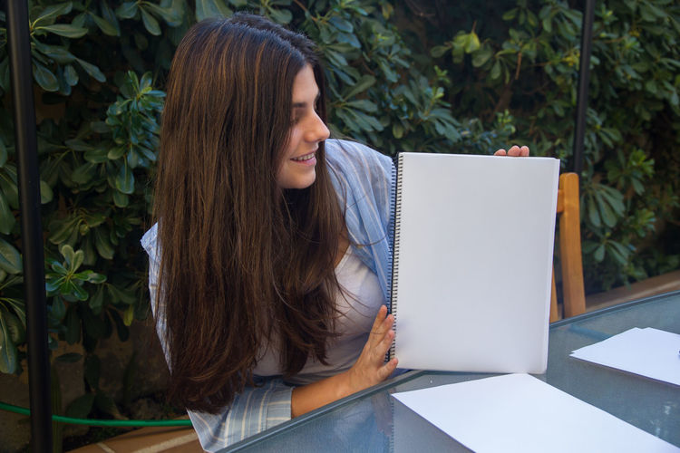 Woman holding spiral notebook against plants
