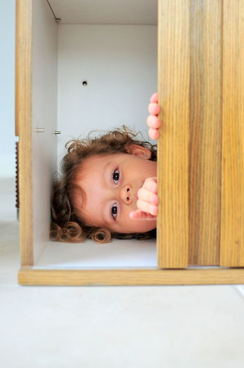 Close-up of girl lying in cabinet at home