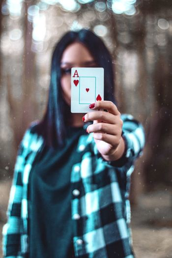 Portrait Of Woman Covering Face With Card