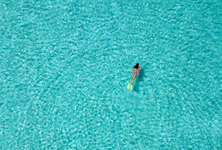 Woman snorkeling in tropical, turquoise waters, aerial view Maldives Snorkeling Vacations Above Adventure Aerial Bikini Day Fins High Angle View Lagoon Leisure Activity Lifestyles Nature Ocean One Person One Woman Only Outdoors Sea Summer Swimming Tropical Turquoise Vacations Water