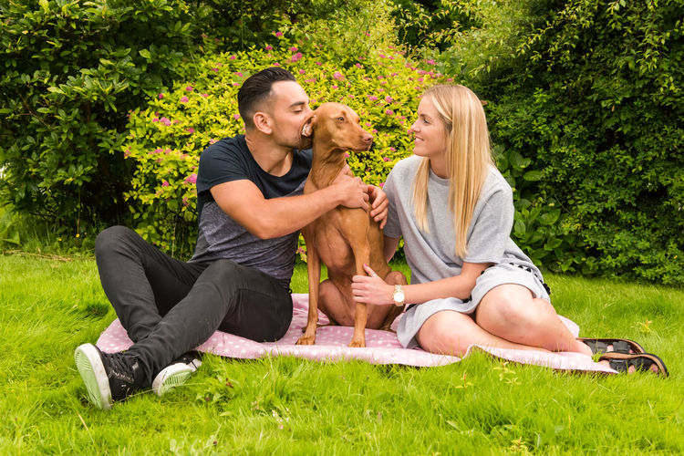 Couple And Vizsla Dog Relaxing On Grass
