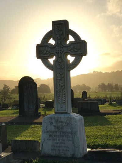 Cross in cemetery against sky during sunset
