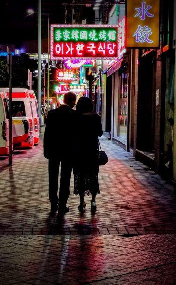 Rear view of women walking on street at night