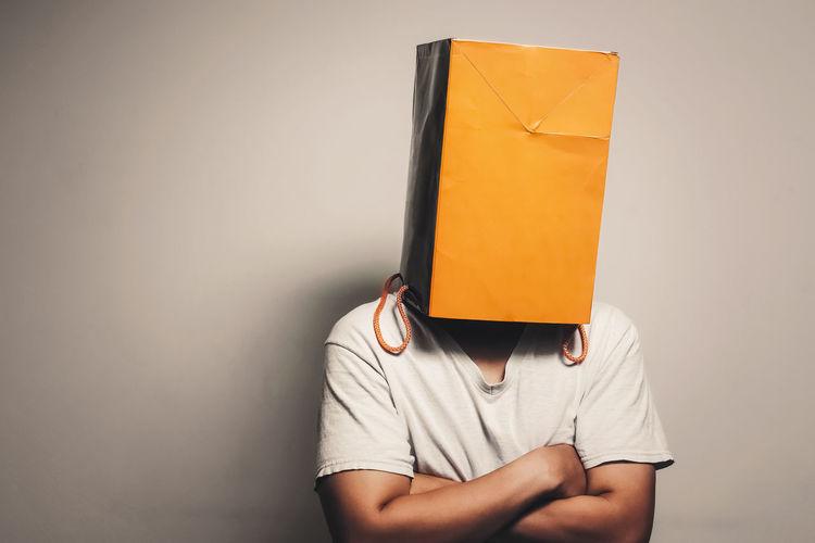 Man wearing paper bag against wall