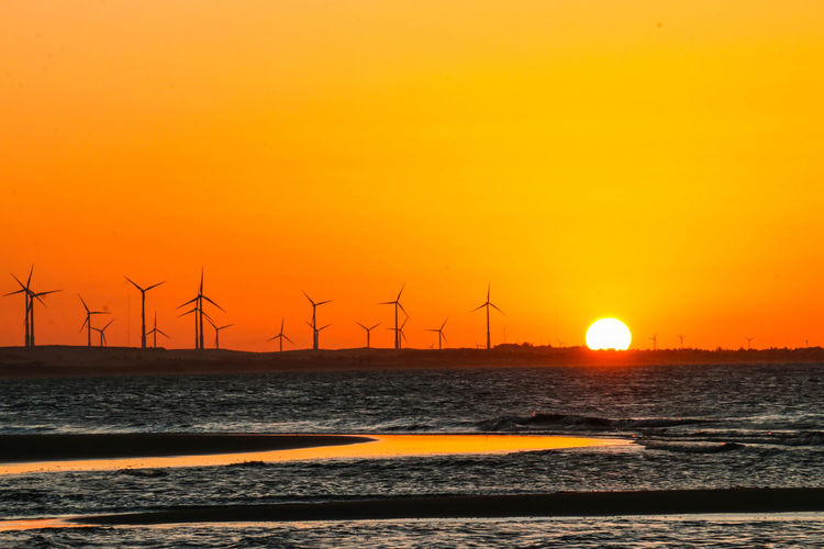 Sea By Windmills Against Clear Sky During Sunset