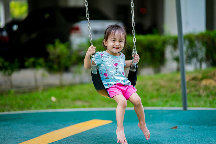 Portrait of smiling girl playing on swing