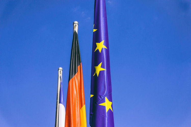 Low Angle View Of Flags Against Clear Blue Sky During Sunny Day