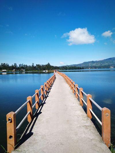 Empty pier over lake against blue sky