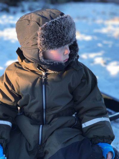 Child Looking Away While Sitting In Snow