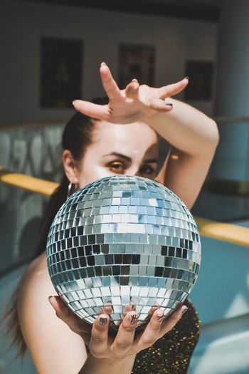 Portrait of woman holding disco ball