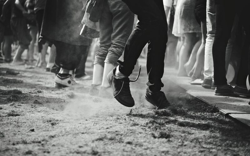 Low Section Of People Blowing Dust While Dancing On Dirt