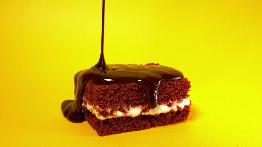 Chocolate topping glaze pouring on biscuit cake dessert on yellow background. Sweet decoration. Cooking, food and baking, pastry shop concept. Sweet Food Food Food And Drink Sweet Dessert Indulgence Temptation Studio Shot Indoors  Cake Unhealthy Eating Baked Chocolate Colored Background Close-up SLICE Freshness Ready-to-eat Yellow No People Slice Of Cake Baked Pastry Item Chocolate Cake Breakfast