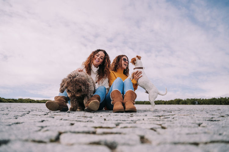 Female friends with dogs sitting on footpath