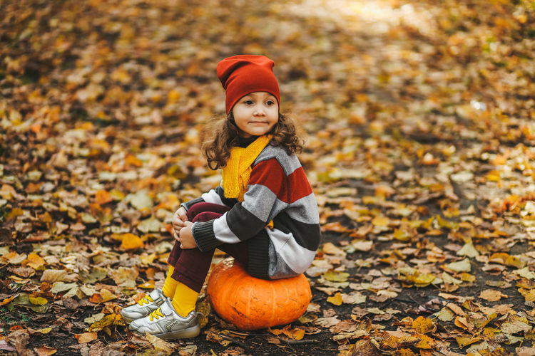 Happy cute little girl child in warm bright clothes sitting on a pumpkin in the autumn forest