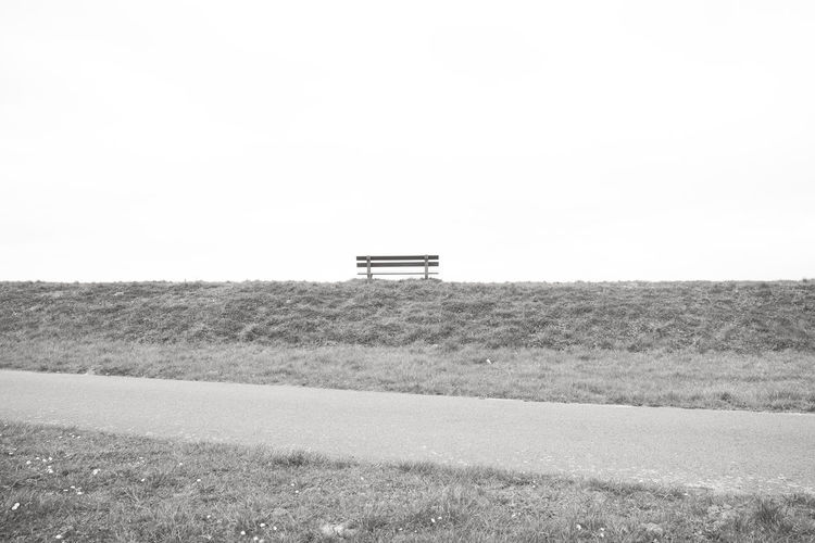A single empty wooden bench on the horizon above a grass field against a large grey clouded sky depicting loneliness, grieve, being alone, sadness Landscape Field Land Environment Day Sky Nature Copy Space Plant Rural Scene No People Scenics - Nature Tranquility Grass Clear Sky Transportation Tranquil Scene Agriculture Mode Of Transportation Outdoors