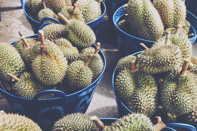 High angle view of durians in containers at market for sale