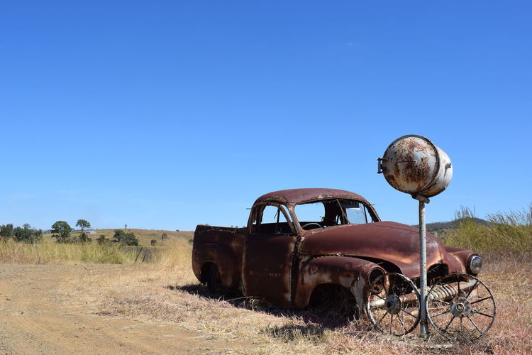 Abandoned truck on field against clear blue sky