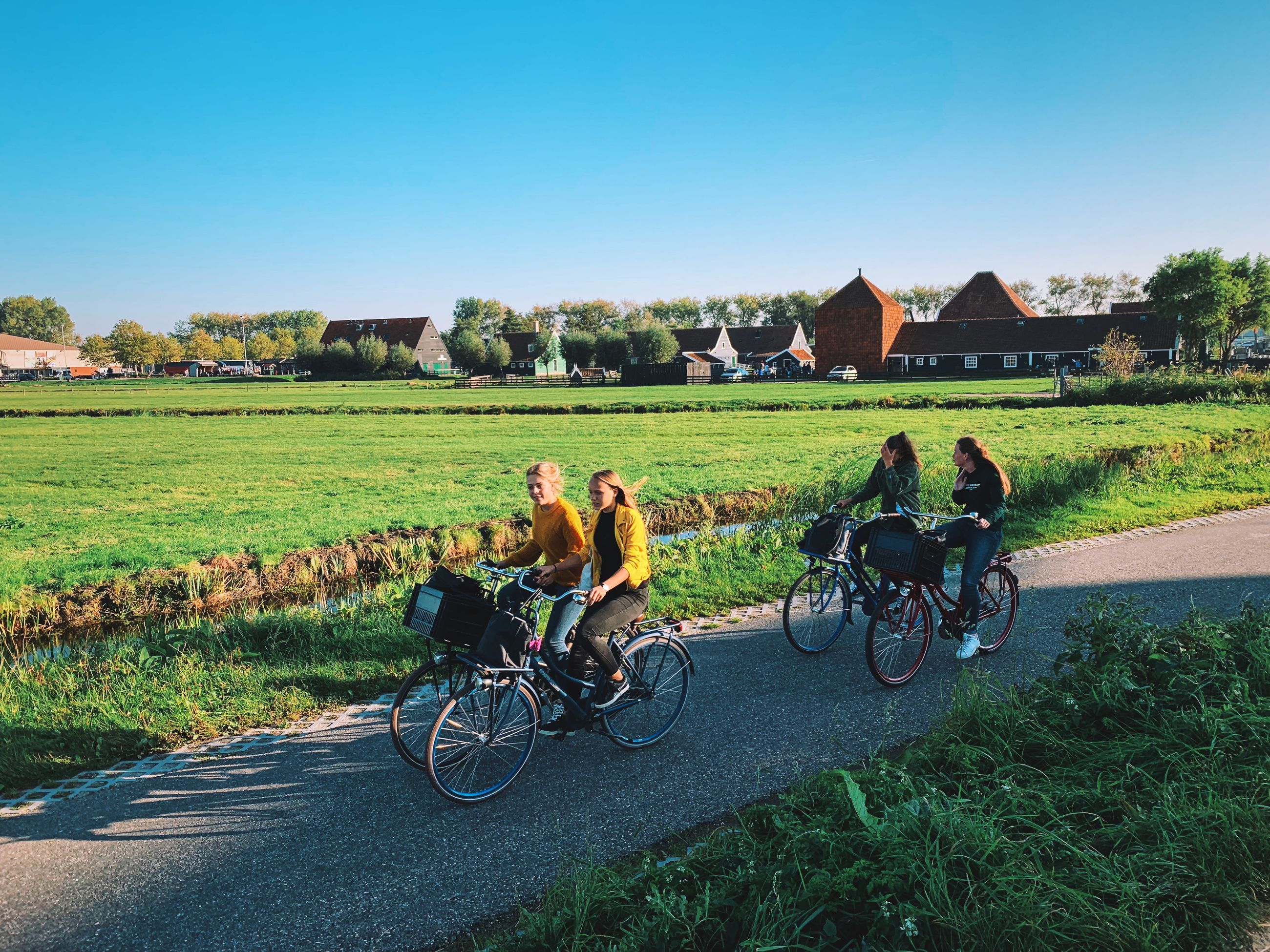 transportation, grass, sky, land vehicle, nature, built structure, bicycle, field, plant, road, architecture, day, real people, group of people, mode of transportation, landscape, men, mammal, building exterior, land, riding, outdoors