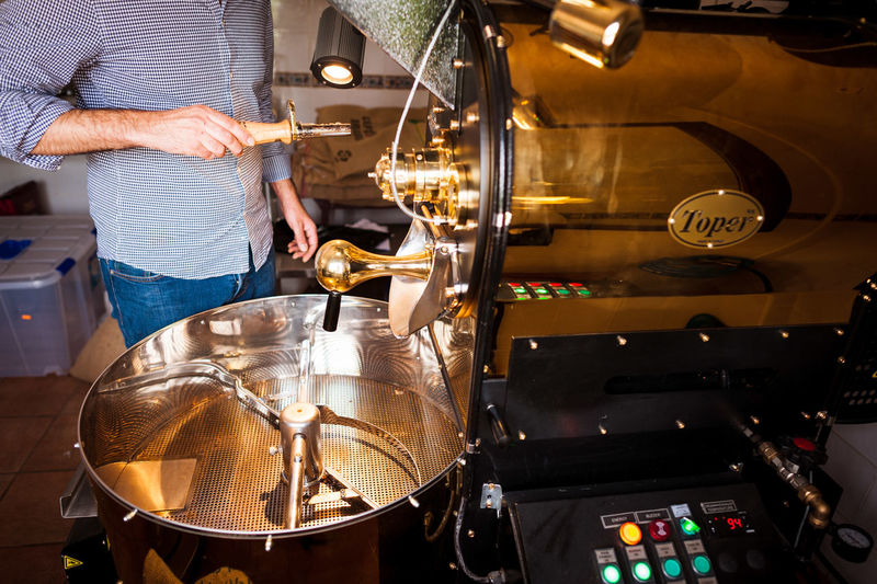 Midsection of man preparing coffee in grinder at shop