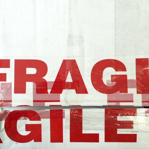 Red fragile tape on white background Capital Letter Close Up Close-up Communication Detail Fragile Information Letters Red Red Letters Text Warning White Color