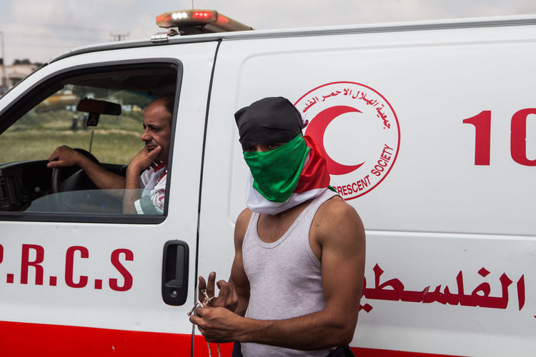 A palestinian with a Slinger in front of an Ambulance in Ramallah during clashes for Nakba day commemoration, on the 15th of May in Palestine. Middle East The Photojournalist - 2018 EyeEm Awards Car Casual Clothing Communication Day Documentary Headshot Journalism Land Vehicle Lifestyles Men Mode Of Transportation Motor Vehicle Occupation People Portrait Real People Reportage Sign Sitting Text Transportation Western Script