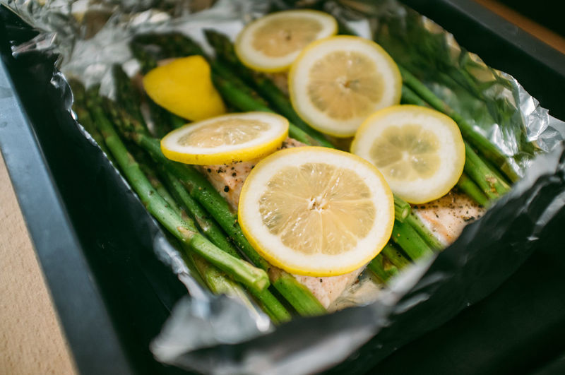 Close-up of lemon slices and asparagus with salmon on foil in container