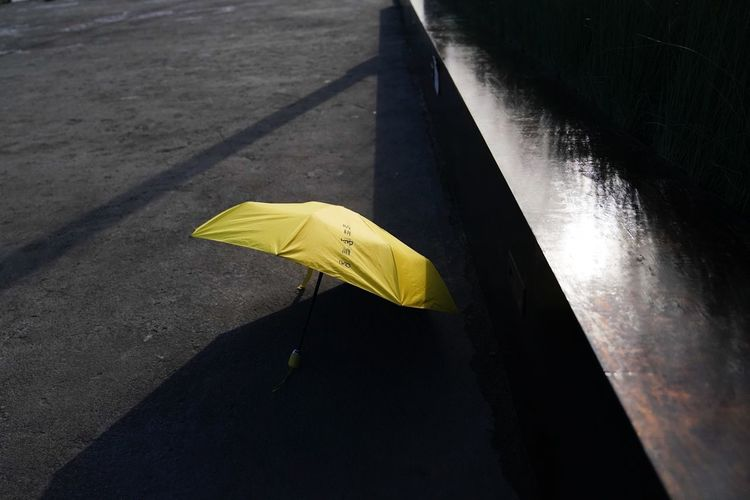 High angle view of yellow umbrella on footpath