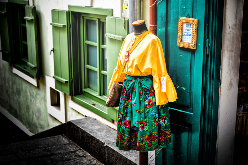 Architecture Building Building Exterior Built Structure Clothing Day Door Entrance Floral Pattern Hanging House Lifestyles One Person Outdoors Real People Rear View Traditional Clothing Uniform Window Women Yellow