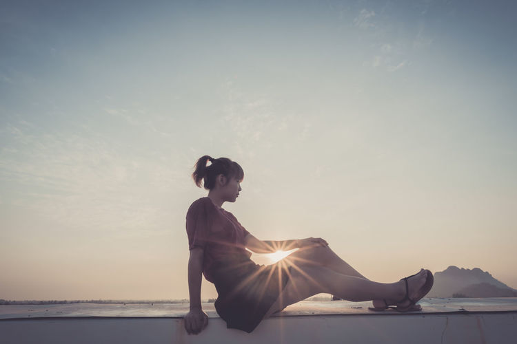 Woman sitting on retaining wall against sky during sunset