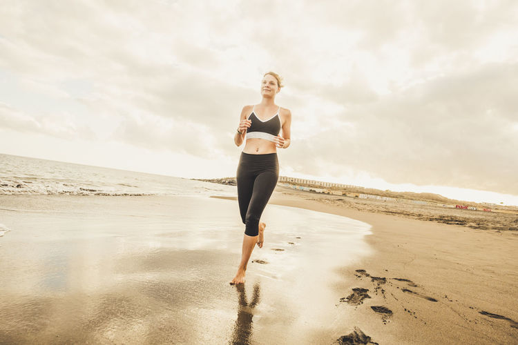 Low angle view of woman running on beach