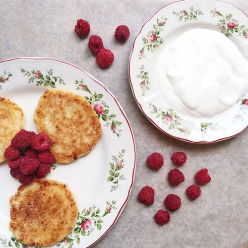 Close-Up Of Fresh Pancakes With Raspberries And Cream In Plate