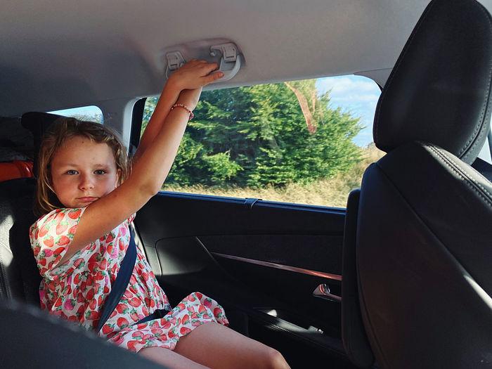 Portrait of girl sitting in car
