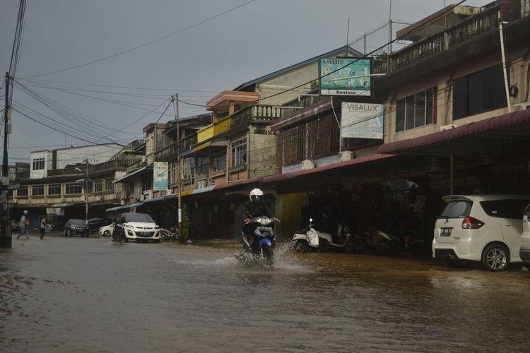 People walking on wet street in city during rainy season